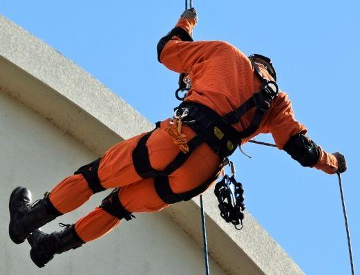 消防の救助隊の特徴であるオレンジを着てバケットを地上に卸す点字をしている本物のレスキュー隊員の画像です